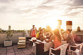Young friends having barbecue party at sunset on penthouse patio - Happy people doing bbq dinner outdoor cooking meat and drinking wine - Focus on left woman face - Food, fun and friendship concept