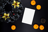 Christmas decor and blank card on black background. White paper with text place. Christmas wreath top view.