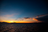 Colorful sunrise with blue sky, orange clouds and rippled sea. Orange blue skyscape in early morning.