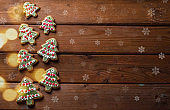 Homemade colorful gingerbread cookies on dark wooden background.