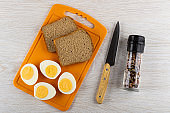 Halves of boiled eggs, bread on cutting board, knife, jar with condiment on wooden table. Top view