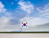 Flag of South Korea with vast meadow and blue sky behind it.