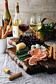 Dishes for a snack Antipasto on a wooden board with prosciutto, different kinds of cheese, grapes and figs on a table with wine