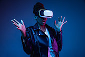 Young african-american woman's using VR-glasses in neon light