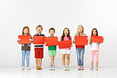 Group of children with red banners isolated in white