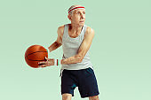 Senior man playing basketball in sportwear isolated on green background