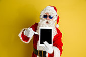 Santa Claus with modern gadgets isolated on yellow studio background