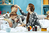 The young parents with sick daughter at home. The ill family.
