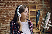 Woman recording music, broadcasting and singing at home