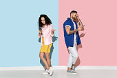 Young emotional man and woman on pink and blue background