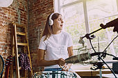 Woman recording music, playing drums and singing at home