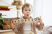 Wooden cubes with word adobtion in hands of little boy