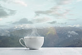Single tea or coffee mug and landscape of mountains on background