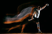 Young handball player against dark studio background in mixed light