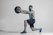 Young caucasian bodybuilder training over studio background