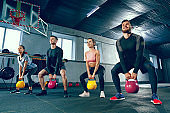 The strong young fitness men and women in sportswear doing exercises at gym