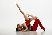 Young graceful couple of ballet dancers dancing on white studio background