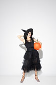 Young woman in hat and dress as a witch on white background