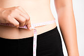 Fat woman hand measuring waist with white measuring tape, reducing excess weight. Healthcare and sport concept.