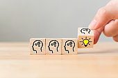 Hand flip over wooden cube block with head human symbol and light bulb icon. Concept creative idea and innovation