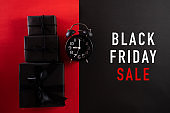 Top view of Black Friday Sale text with black gift box with Alarm clock on white background. Shopping concept boxing day and black Friday composition.