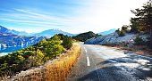 Beautiful asphalt curved mountain road in the french Alps near lake Lac de Serre-Poncon on a clear sunny day