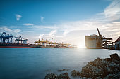 Cargo ship at Trade Port harbor with crane and blue sky