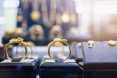 Jewelry golden rings earrings and necklaces show in luxury retail store window display showcase