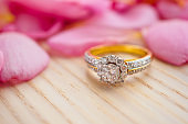 Jewelry diamond ring on wood table with beautiful pink rose petal background close up