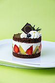 Chocolate cake with whip cream and fruit. Set on green background.