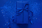 Blue gift or present box with blue glitter and silver star shaped confetti on blue background. Festive concept.