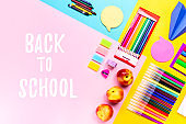 Back to school with school supplies, stationery, backpack and lunchbox with funny food for kids on multicolor desk