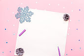 Woman manicured hands holding pen and writing goals and plans for new year. Flat lay on pastel pink desk with confetti and christmas decorations, top view, copy space
