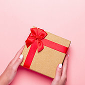 Woman manicured hands holding red and golden wrapped present or gift box on pastel pink background, copy space, top view, flat lay. Background for Valentine's Day, Mother's Day.