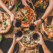 People clinking glasses over table with Italian pizza, square crop