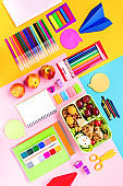 School supplies and lunchbox with food for kids. Colorful stationery layout on multicolor background, copy space