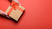 Woman manicured hands holding red and golden wrapped present or gift box on orange brown background, copy space, top view, flat lay. Background for Valentine's Day, Mother's Day.