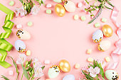 Festive Happy Easter background with decorated eggs, flowers, candy and ribbons in pastel colors on pink. Copy space