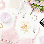 Feminine flat lay with women fashion accessories, lingerie, jewelry, cosmetics, coffee and flowers. Top view