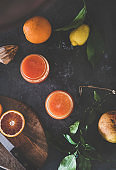 Flat-lay of orange juice in glasses and fresh fruits