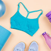 Fitness equipment. Woman workout accessories and clothes flat lay. Top view