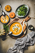 Flat-lay of pumpkin cream soup with seeds, parsley and bread