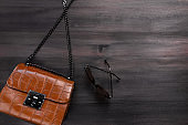 Woman crocodile leather purse or handbag on chain closeup, casual style, top view, copy space