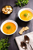 Pumpkin cream soup with croutons and fresh dill and parsley on dark wooden background, top view