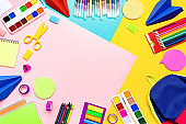 School supplies with colorful stationery. Markers, pencils, notebooks, backpack on multicolor background, copy space