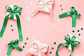 Giftboxes with pink and green ribbons and golden confetti frame on pastel pink background, copy space.