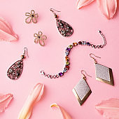 Glamorous woman accessories and jewelry. Feminine composition on pink background with lily flower
