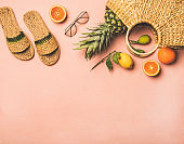 Summer apparel items and fresh fruits over pastel pink background