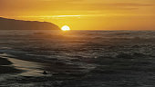 close view of the sun setting at kaena point in hawaii