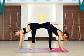 Couple womans in gym do yoga stretching exercises. Fit and wellness lifestyle